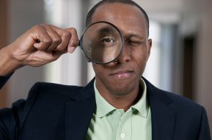 Man holding up a magnifying glass