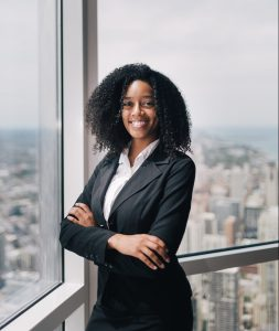 Tiara Starks smiling with arms folded in front of floor to ceiling windows with a city view